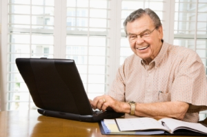 Mature Caucasian man typing on laptop in home.